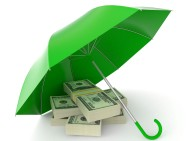 A bright green umbrella sits open on the ground over a stack of cash